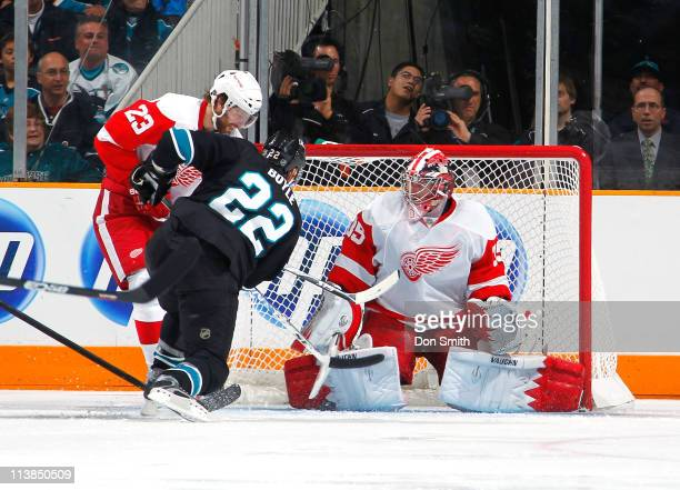 Dan Boyle of the San Jose Sharks takes a shot against Jimmy Howard and Brad Stuart of the Detroit Red Wings in Game Five of the Western Conference...