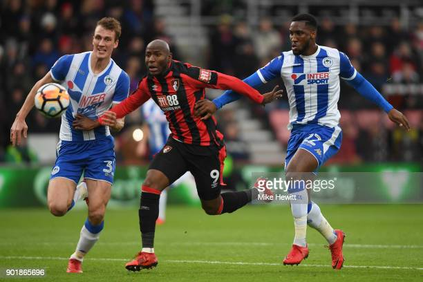 Dan Burn and Cheyenne Dunkley of Wigan Athletic challenge Benik Afobe of AFC Bournemouth during the The Emirates FA Cup Third Round match between AFC...