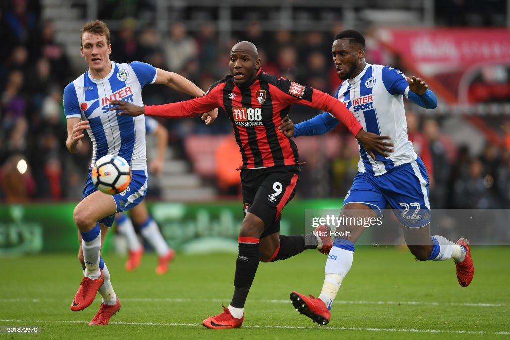 Dan Burn (L) and Cheyenne Dunkley of Wigan Athletic challenge Benik Afobe of AFC Bournemouth during the The Emirates FA Cup Third Round match between AFC Bournemouth and Wigan Athletic at Vitality Stadium on January 6, 2018 in Bournemouth, England.