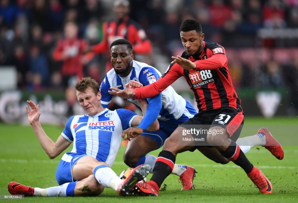Dan Burn (L) and Cheyenne Dunkley of Wigan Athletic challenge Lys Mousset of AFC Bournemouth during the The Emirates FA Cup Third Round match between AFC Bournemouth and Wigan Athletic at Vitality Stadium on January 6, 2018 in Bournemouth, England.