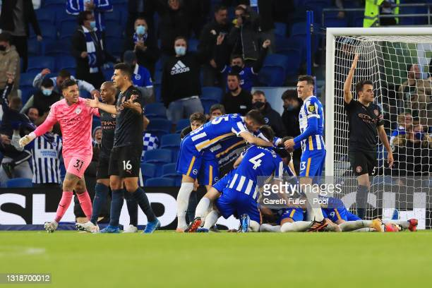 Dan Burn of Brighton and Hove Albion celebrates with team mates after scoring their side's third goal during the Premier League match between...