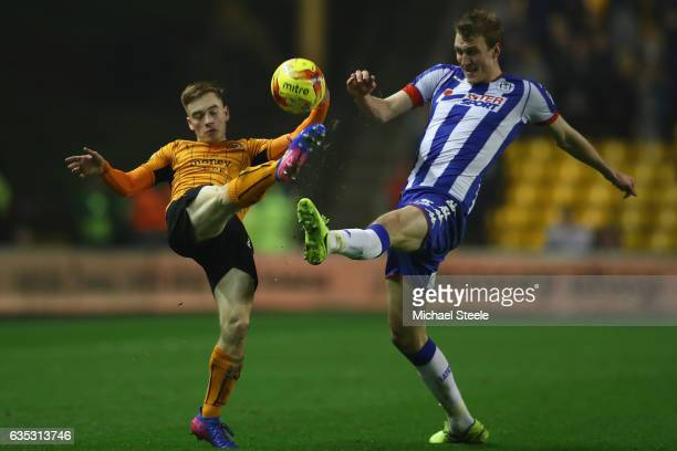 Dan Burn of Wigan challenges Connor Ronan of Wolverhampton during the Sky Bet Championship match between Wolverhampton Wanderers and Wigan Athletic...