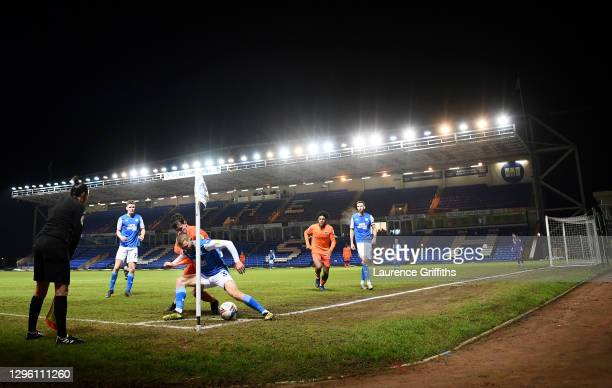 Dan Butler of Peterborough United defends the ball in the corner under pressure from Harry Kavanagh of Portsmouth during the Papa John's Trophy match...