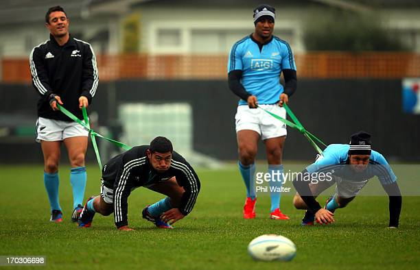 Dan Carter and Julian Savea hold onto Charles Piutau and Ben Smith during a New Zealand All Blacks training session at Linfield Park on June 11 2013...