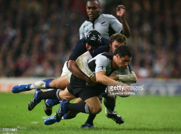 Dan Carter of New Zealand is tackled by Vincent Clerc of France during the Quarter Final of the Rugby World Cup 2007 match between New Zealand and...
