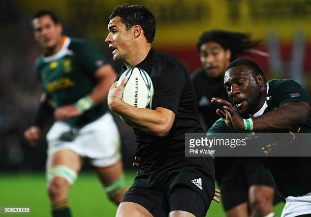 Dan Carter of New Zealand runs past Tendai Mtawarira of South Africa during the Tri Nations Test between the New Zealand All Blacks and South African...