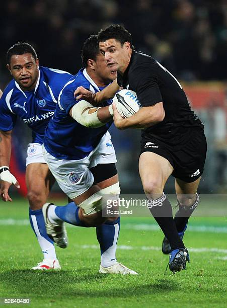 Dan Carter of the All Blacks fends off a tackle during the rugby test match between New Zealand and Samoa at Yarrows Stadium on September 3 2008 in...