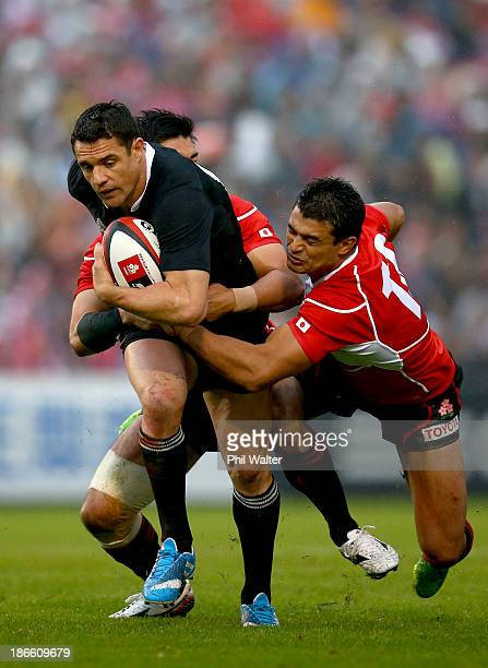 Dan Carter of the All Blacks is tackled by Craig Wing of Japan during the International Rugby Test Match between Japan and the New Zealand All Blacks...