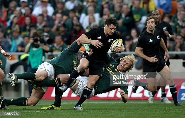 Dan Carter of the All Blacks is tackled by Schalk Burger and Gurthro Steenkamp during the 2010 Tri-Nations match between the South African Springboks...