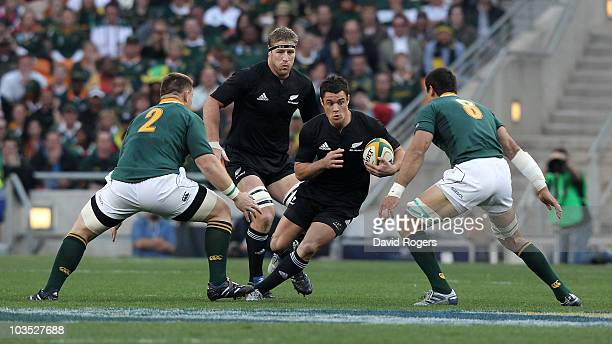 Dan Carter of the All Blacks races past John Smit and Pierre Spies during the 2010 TriNations match between the South African Springboks and the New...