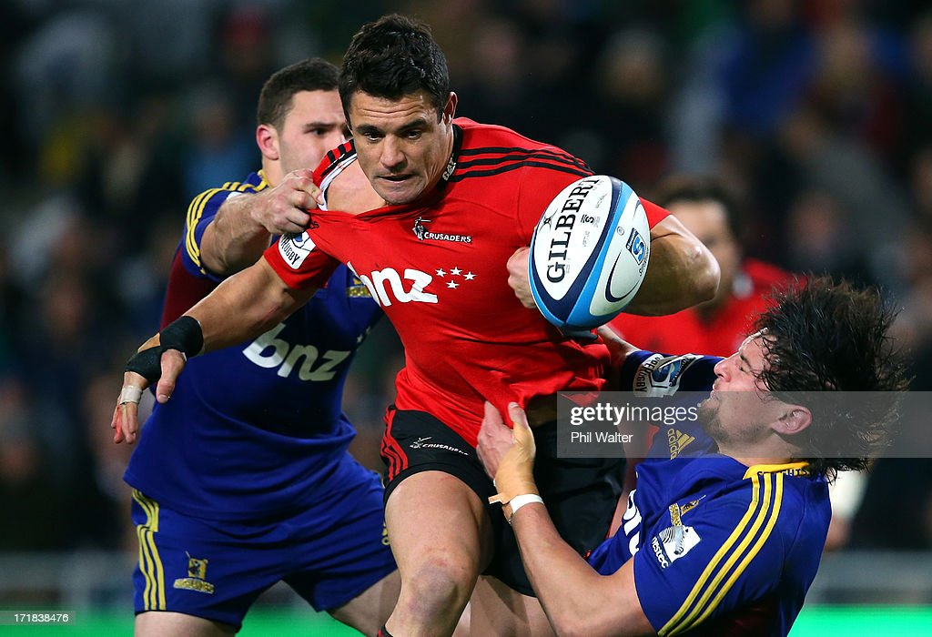Dan Carter of the Crusaders is tackled by Elliot Dixon (R) of the Highlanders during the round 18 Super Rugby match between the Highlanders and the Crusaders at Forsyth Barr Stadium on June 29, 2013 in Dunedin, New Zealand.