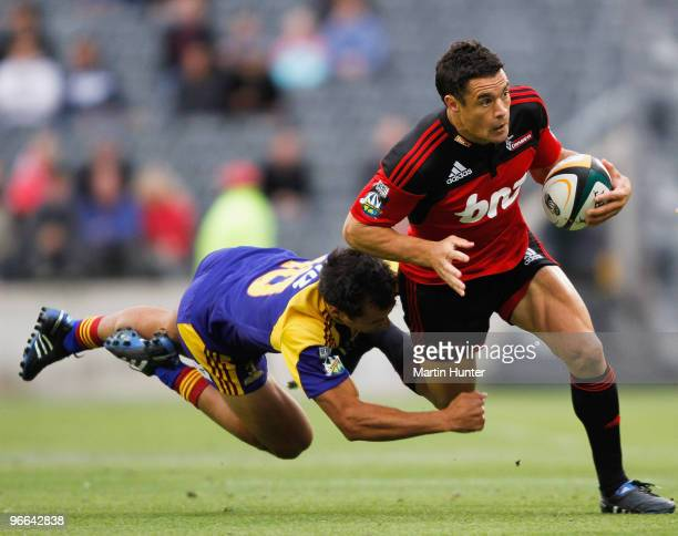 Dan Carter of the Crusaders is tackled by Matt Berquist of the Highlanders during the round one Super 14 match between the Crusaders and the...