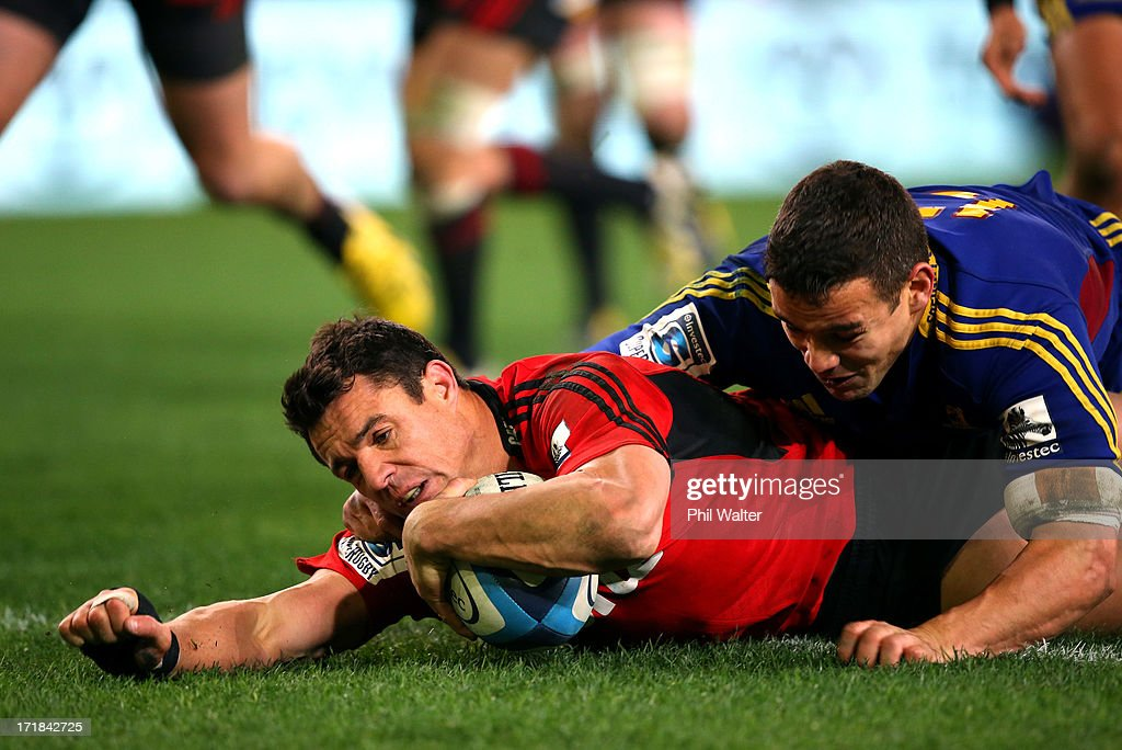 Dan Carter of the Crusaders scores a try in the tackle of Tamati Ellison of the Highlanders during the round 18 Super Rugby match between the Highlanders and the Crusaders at Forsyth Barr Stadium on June 29, 2013 in Dunedin, New Zealand.