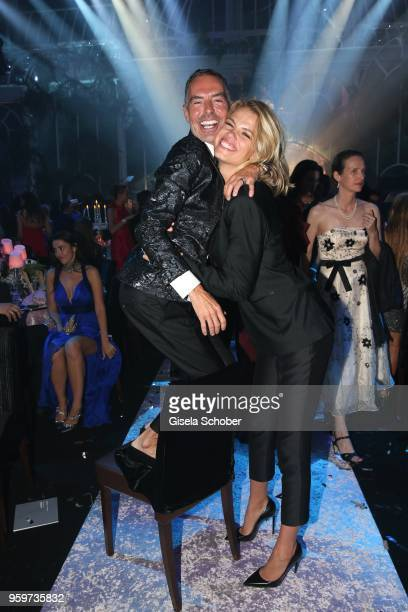 Dan Caten on a chair and Hailey Clauson attend the amfAR Gala Cannes 2018 dinner at Hotel du CapEdenRoc on May 17 2018 in Cap d'Antibes France