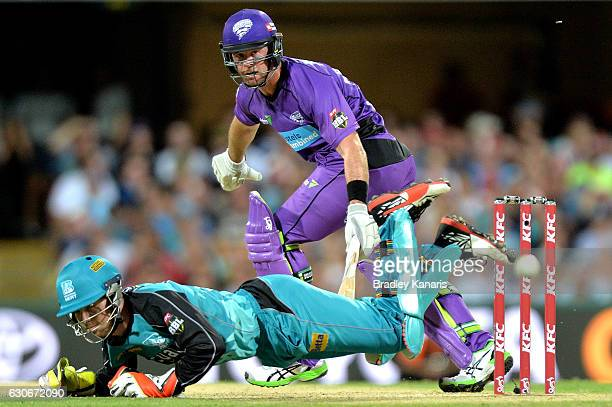 Dan Christian of the Hurricanes gets the ball past wicketkeeper Jimmy Peirson of the Heat during the Big Bash League between the Brisbane Heat and...