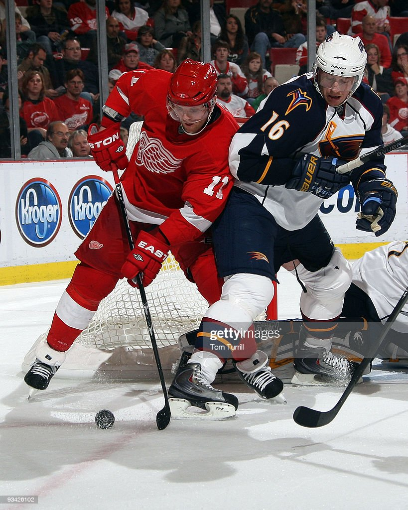 Dan Cleary #11 of the Detroit Red Wings and Christoph Schubert #16 of the Atlanta Thrashers battle for the puck in front of the net during a NHL game at Joe Louis Arena on November 25, 2009 in Detroit, Michigan.