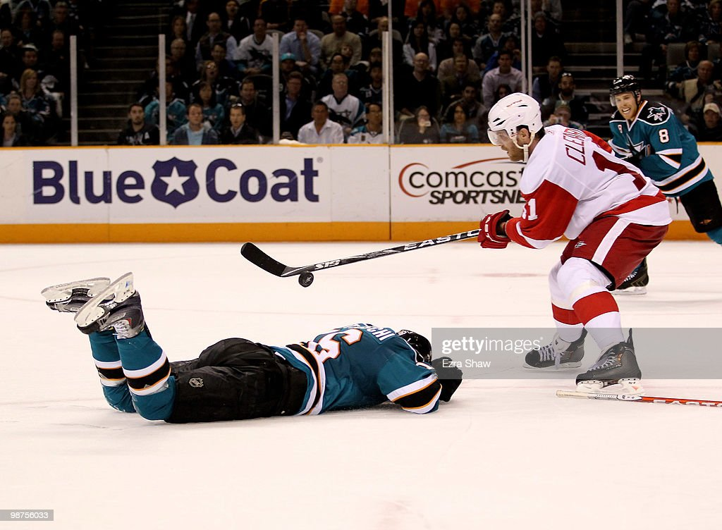 Dan Cleary #11 of the Detroit Red Wings controls the puck while Devin Setoguchi #16 of the San Jose Sharks lies injured on the ice in Game One of the Western Conference Semifinals during the 2010 NHL Stanley Cup Playoffs at HP Pavilion on April 29, 2010 in San Jose, California.