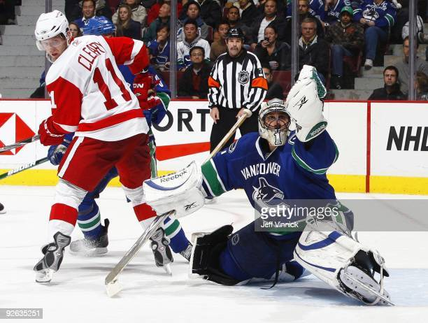 Dan Cleary of the Detroit Red Wings looks for a rebound as Roberto Luongo of the Vancouver Canucks makes a glove save during their game at General...