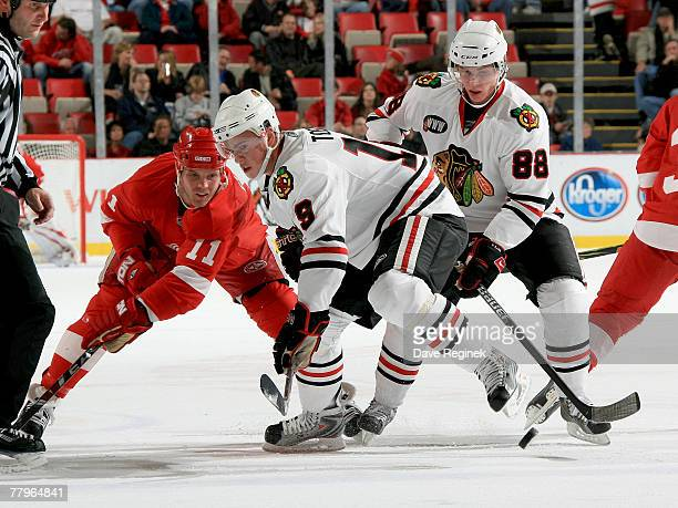 Dan Cleary of the Detroit Red Wings loses a face off against Jonathan Toews and Patrick Kane of the the Chicago Blackhawks during an NHL game at Joe...