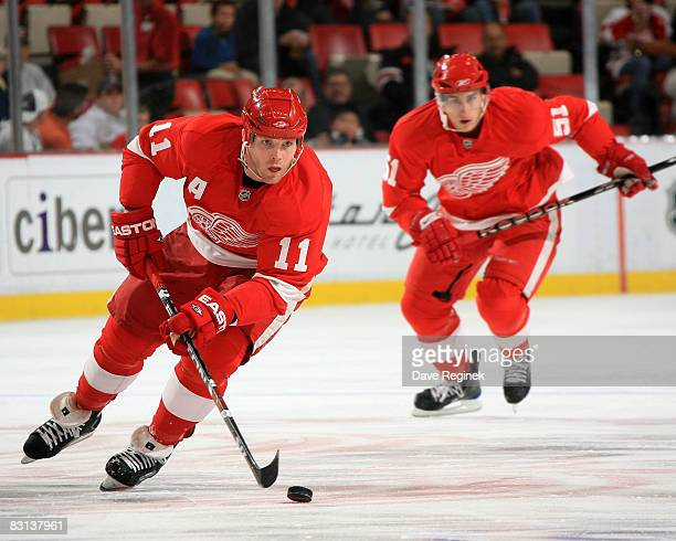 Dan Cleary of the Detroit Red Wings skates up ice with the puck with teammate Valtteri Filppula following behind during a NHL preseason game against...