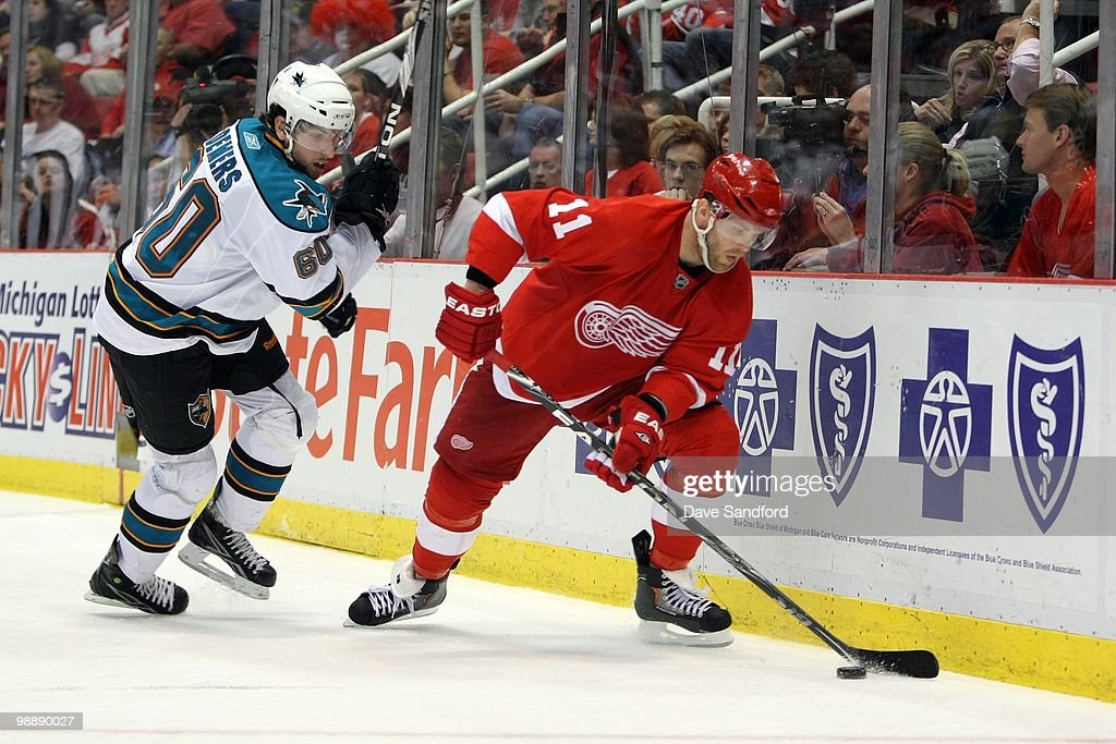 Dan Cleary #11 of the Detroit Red Wings skates with the puck against Jason Demers #60 of the San Jose Sharks in Game Three of the Western Conference Semifinals during the 2010 Stanley Cup Playoffs at Joe Louis Arena on May 4, 2010 in Detroit, Michigan.