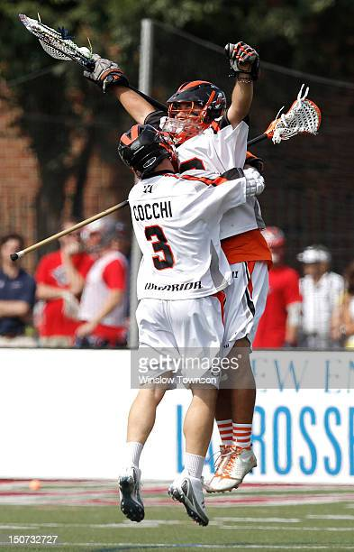 Dan Cocchi of the Denver Outlaws celebrates with goalie Jesse Schwartzman after defeating the Long Island Lizards 1312 in a MLL semifinal game at...