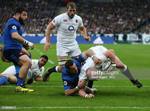 Dan Cole of England drves to the line to score his team's second try despite the tackle from Scott Spedding of France during the RBS Six Nations...