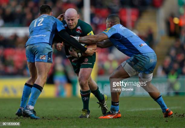 Dan Cole of Leicester Tigers tackled by Johnny Williams and Joe Cokanasiga of London Irish during the Aviva Premiership match between Leicester...