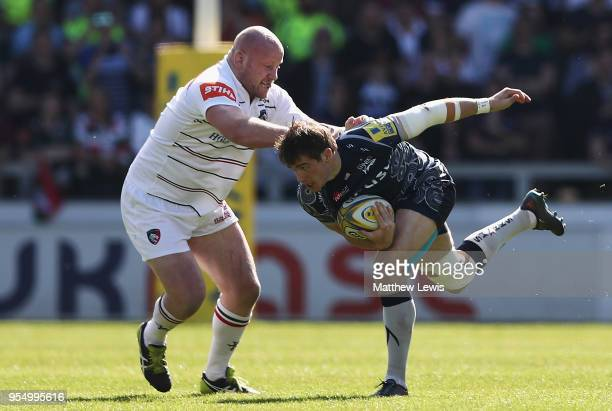 Dan Cole of Leicester Tigers tackles AJ MacGinty of Sale Sharks during the Aviva Premiership match between Sale Sharks and Leicester Tigers at AJ...