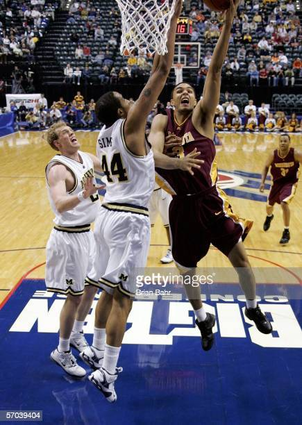 Dan Coleman of the Minnesota Golden Gophers lays the ball up over Courtney Sims of the Michigan Wolverines during Day 1 of the Big 10 Tournament on...