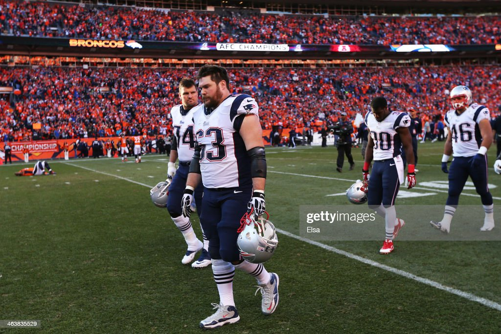 Dan Connolly #63 of the New England Patriots and teammates walk off of the field after loosing to the Denver Broncos 16 to 26 during the AFC Championship game at Sports Authority Field at Mile High on January 19, 2014 in Denver, Colorado.