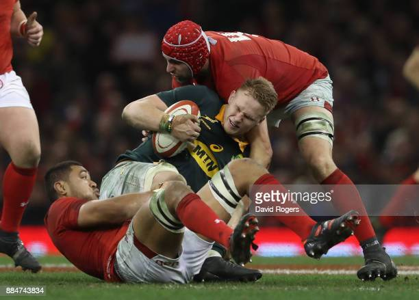 Dan du Preez of South Africa is tackled by Taulupe Faletau and Cory Hill during the rugby union international match between Wales and South Africa at...