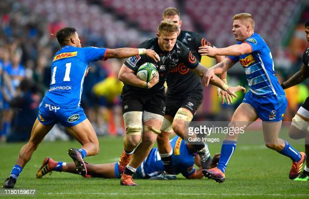 Dan du Preez of The Sharks tackled by Edwill van der Merwe of the Stormers and Justin Phillips of the Stormers during the Super Rugby match between...