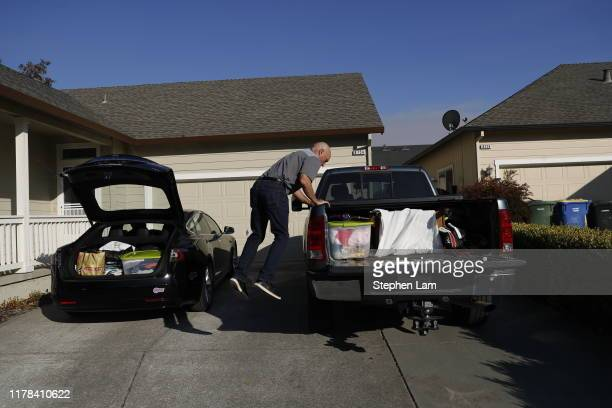 Dan Duran leaps from his car as he prepares to evacuate from his home in anticipation of the expected wind event on October 26 2019 in Windsor...