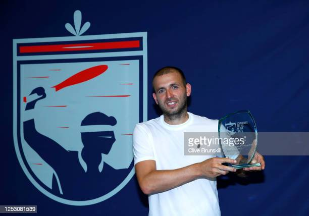 Dan Evans celebrates with the winners trophy following the final against Kyle Edmund during day 6 of Schroders Battle of the Brits at National Tennis...