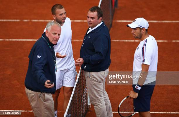 Dan Evans of Great Britain argues with match officials after being made to play on during heavy rain and lightning in the final quqlifying round...
