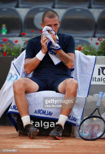 Dan Evans of Great Britain reacts as he sits down during a change of ends in his round one match against Hubert Hurkacz of Poland during day one of...