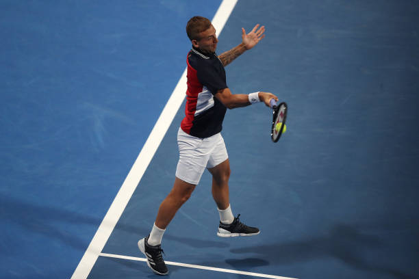 Dan Evans of Great Britain returns a forehand in his match against Roger Federer of Switzerland on Day 3 of the Qatar ExxonMobil Open at Khalifa...