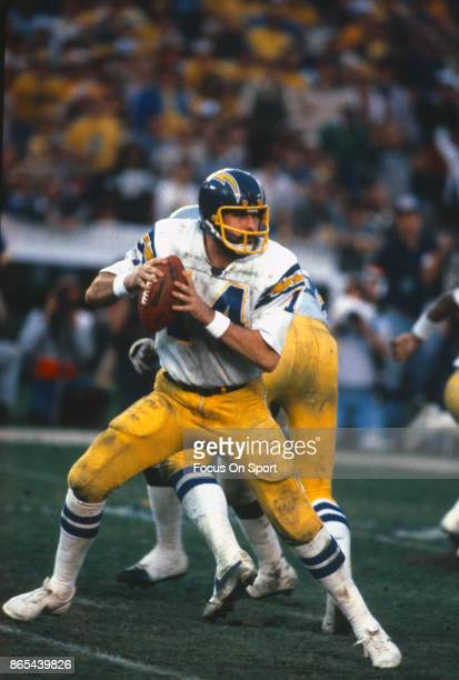 Dan Fouts of the San Diego Chargers drops back to pass against the Oakland Raiders during an NFL football game circa 1980 at Jack Murphy Stadium in...