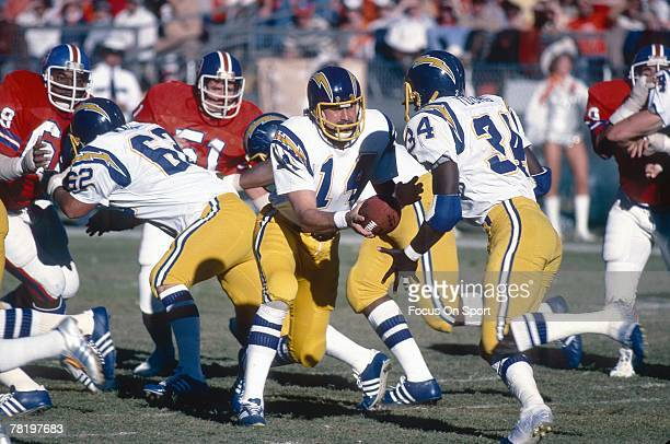 Dan Fouts of the San Diego Chargers turns to hand the ball off to running back Rickey Young aginst the Denver Broncos in a circa mid 1970's NFL...