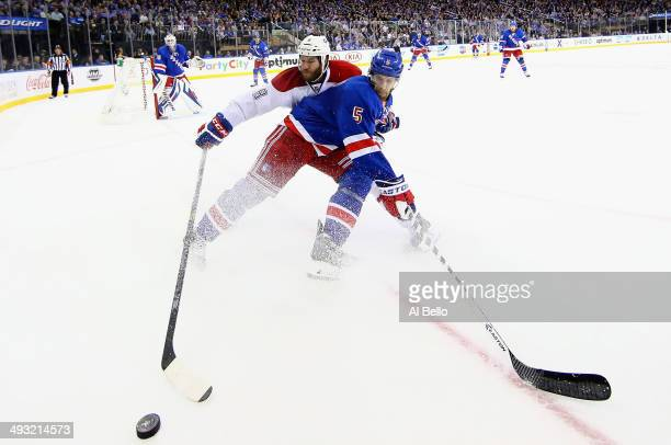 Dan Girardi of the New York Rangers and Brandon Prust of the Montreal Canadiens battle for the puck along the boards in Game Three of the Eastern...