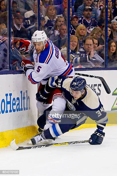 Dan Girardi of the New York Rangers and Josh Anderson of the Columbus Blue Jackets battle for control of a loose puck during the second period on...