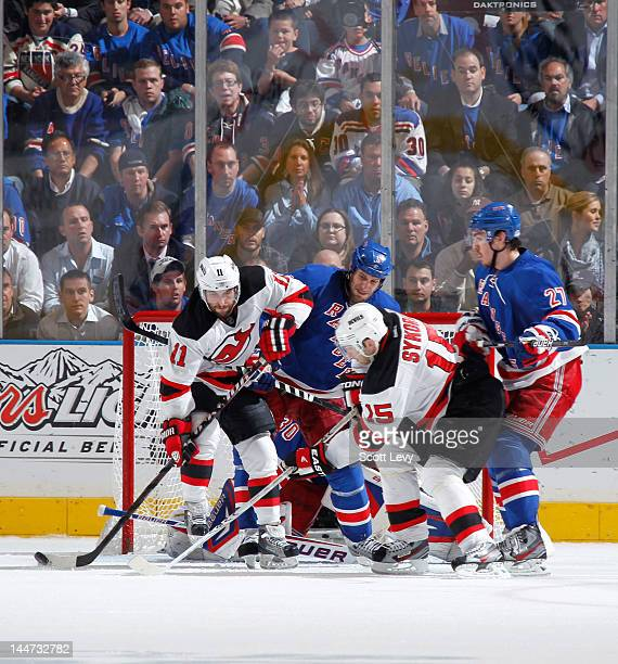 Dan Girardi of the New York Rangers defends against Stephen Gionta and Petr Sykora of the New Jersey Devils in Game One of the Eastern Conference...