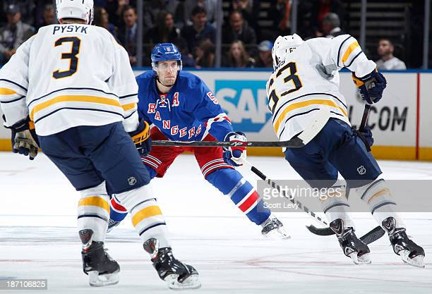 Dan Girardi of the New York Rangers defends against Tyler Ennis of the Buffalo Sabres at Madison Square Garden on October 31 2013 in New York City...