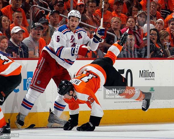 Dan Girardi of the New York Rangers hits Jesper Fast of the New York Rangers during the first period in Game Three of the First Round of the 2014 NHL...