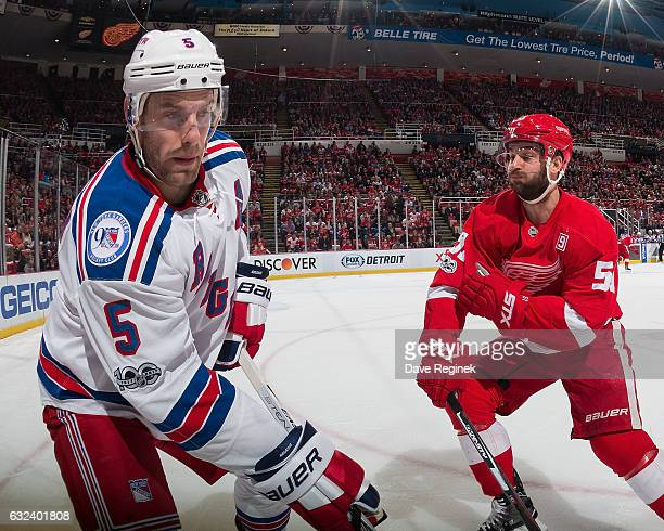 Dan Girardi of the New York Rangers looks to pass the puck as Frans Nielsen of the Detroit Red Wings comes in for a hit during an NHL game at Joe...