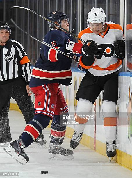 Dan Girardi of the New York Rangers throws a hit against Brayden Schenn of the Philadelphia Flyers at Madison Square Garden on November 29 2014 in...