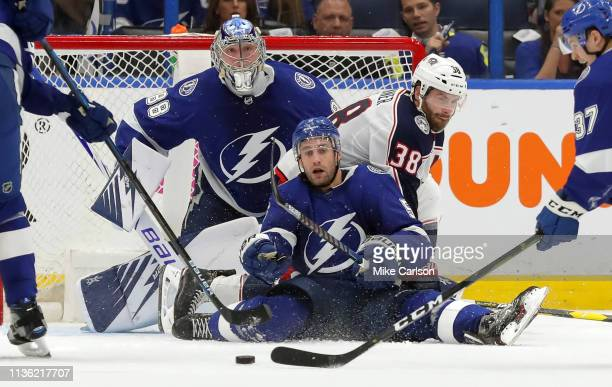 Dan Girardi of the Tampa Bay Lightning defends against Boone Jenner of the Columbus Blue Jackets as goaltender Andrei Vasilevskiy looks at the...