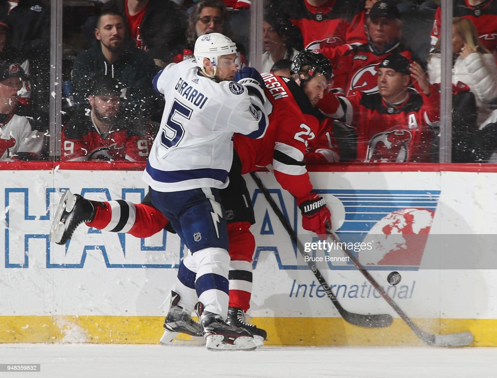 Dan Girardi #5 of the Tampa Bay Lightning hits Stefan Noesen #23 of the New Jersey Devils into the boards during the third period in Game Four of the Eastern Conference First Round during the 2018 NHL Stanley Cup Playoffs at the Prudential Center on April 18, 2018 in Newark, New Jersey. The Lightning defeated the Devils 3-1.