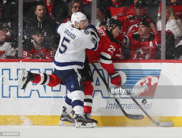 Dan Girardi of the Tampa Bay Lightning hits Stefan Noesen of the New Jersey Devils into the boards during the third period in Game Four of the...